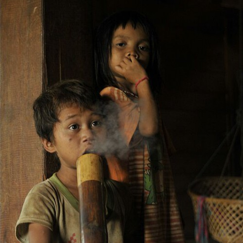Children and adults alike smoke from a bamboo tobacco bong in some small villages in Lao